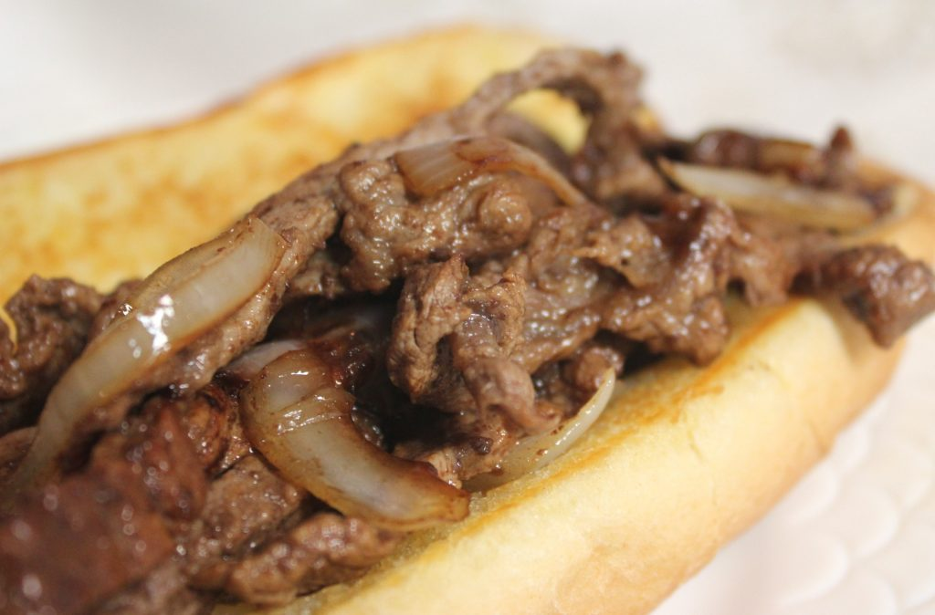 Beef and onion on a toasted bun sandwich