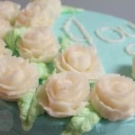 Cake with Tiffany Blue buttercream icing, flowers and word Joy