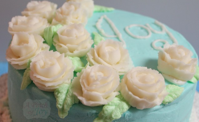 Cake with Tiffany Blue frosting, flowers and word Joy