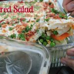 Lettuce salad layered with other vegetables and topped with mayo