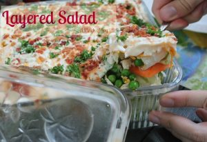 Lettuce salad layered with other vegetables and topped with mayo - A Pinch of Joy